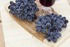 Bunch of fresh blue grapes on a wooden board Royalty Free Stock Image