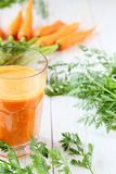 Bunch of fresh carrots and a glass of juice Stock Image