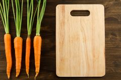 Bunch of fresh carrots with green leaves and cutting board Royalty Free Stock Images