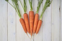 Bunch of fresh carrots with green leaves over white wooden background royalty free stock photos