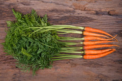 Bunch of fresh carrots with green leaves over wooden background Royalty Free Stock Images