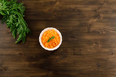 Bunch of fresh carrots with green leaves on wooden . Cooking carrot salad. Stock Photo