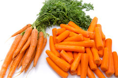 Bunch of fresh carrots and heap of peeled carrots Royalty Free Stock Photography