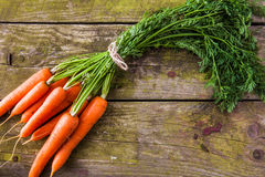 Bunch of fresh carrots on a rustic background Royalty Free Stock Photos