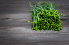 Bunch of fresh chives on a wooden cutting board, selective focus. Green onions on a black wooden background. Onions on old wood. Fresh onion. Green onion (Food Royalty Free Stock Images