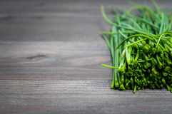 Bunch of fresh chives on a wooden cutting board, selective focus. Green onions on a black wooden background. Onions on old wood. Fresh onion. Green onion (Food Stock Photography