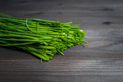 Bunch of fresh chives on a wooden cutting board, selective focus. Green onions on a black wooden background. Onions on old wood. Fresh onion. Green onion (Food Royalty Free Stock Photography