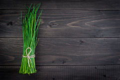 Bunch of fresh chives on a wooden cutting board, selective focus. Green onions on a black wooden background. Onions on old wood. Fresh onion. Green onion (Food Stock Photos