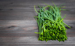 Bunch of fresh chives on a wooden cutting board, selective focus. Green onions on a black wooden background. Onions on old wood. Fresh onion. Green onion (Food Royalty Free Stock Photos