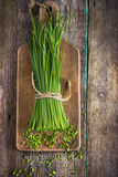 Bunch of fresh chives on a wooden cutting board Stock Photo