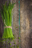 Bunch of fresh chives on a wooden cutting board Royalty Free Stock Photos