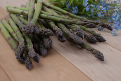 Bunch of Fresh Crispy Green  Asparagus with Forget Me Flowers Royalty Free Stock Images