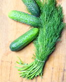 Bunch fresh dill and cucumbers on wooden table Royalty Free Stock Photo