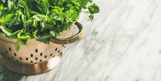 Bunch of fresh garden herbs in brass colander, copy space stock image