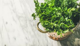 Bunch of fresh garden herbs in brass colander, horizontal composition royalty free stock photos