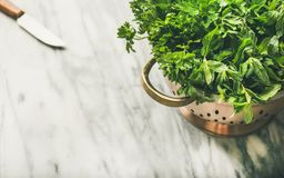 Bunch of fresh garden herbs in brass colander, marble background stock image