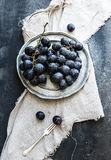 Bunch of fresh grapes in rustic vetal plate on dark grunge background Royalty Free Stock Images