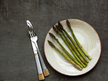 Bunch of fresh green asparagus in clay plate on grey background Stock Image
