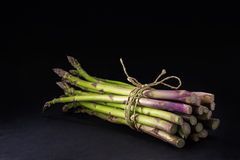 Bunch of fresh green asparagus on a dark background, copy space Royalty Free Stock Photos