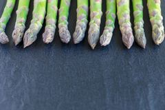 Bunch of fresh green asparagus on dark slate background, horizon Royalty Free Stock Image