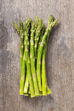 Bunch of fresh green asparagus on old wood board. Rustic style Royalty Free Stock Photo