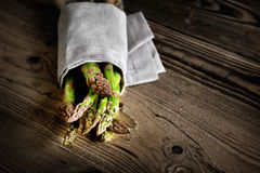 Bunch of fresh green asparagus over dark wooden table Royalty Free Stock Photos