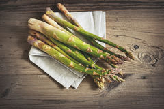 Bunch of fresh green asparagus over dark wooden table Royalty Free Stock Photo