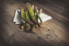 Bunch of fresh green asparagus over dark wooden table Stock Photography