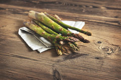 Bunch of fresh green asparagus over dark wooden table Stock Images