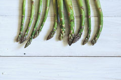 Bunch of fresh green asparagus over white wooden table Stock Photos
