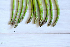 Bunch of fresh green asparagus over white wooden table Royalty Free Stock Images