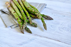 Bunch of fresh green asparagus over white wooden table Royalty Free Stock Photos