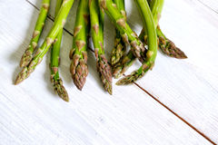 Bunch of fresh green asparagus over white wooden table Stock Photography
