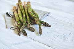 Bunch of fresh green asparagus over white wooden table Stock Images