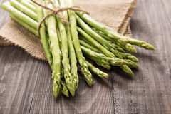 Bunch of fresh green asparagus on a rustic wooden table Royalty Free Stock Images