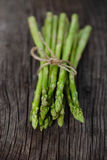 Bunch of fresh green asparagus spears. Tied with string on a rustic wooden table royalty free stock photo