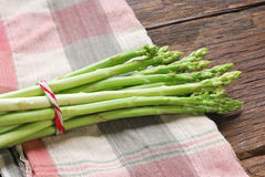 Bunch of fresh green asparagus spears on a rustic wooden Stock Photos