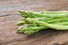 Bunch of fresh green asparagus spears on a rustic wooden Stock Images