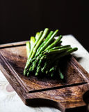 Bunch of fresh green asparagus spears tied with twine on a rusti Stock Photos