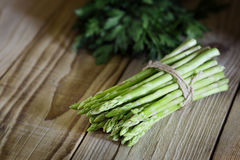 Bunch of fresh green asparagus on a wooden table. Bunch of fresh green asparagus bandaged with a rope. Fresh asparagus on a wooden table in a rustic style. Low royalty free stock images