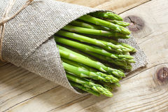 Bunch of fresh green asparagus on a wooden table. Bunch of fresh green asparagus wrapped in burlap and bandaged with a rope. Fresh asparagus on a wooden table stock image