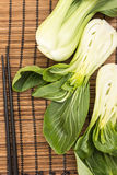 Bunch of fresh green baby bok choy with chopsticks , on bamboo placemat Stock Photos