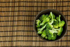 Bunch of fresh green broccoli in dark brown bowl over wooden background. Royalty Free Stock Image