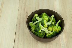 Bunch of fresh green broccoli in dark brown bowl over wooden background. Royalty Free Stock Photography