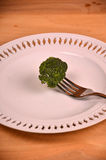 Bunch of fresh green broccoli on white plate over wooden background Royalty Free Stock Photo