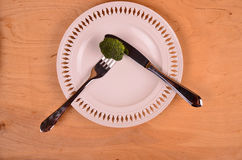 Bunch of fresh green broccoli on white plate over wooden background Royalty Free Stock Photography