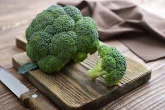 Bunch of fresh green broccoli. On wooden cutting board closeup Stock Image