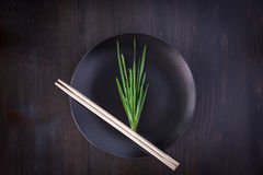Bunch of fresh herbs on an empty black plate with chopsticks Royalty Free Stock Photo