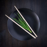 Bunch of fresh herbs on an empty black plate with chopsticks Stock Image