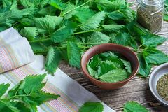 A bunch of fresh nettle on a wooden table. A bunch of nettle on a wooden table for cooking stock photo